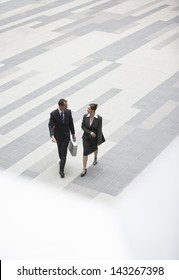 High angle view of businessman and businesswoman walking in outdoor plaza