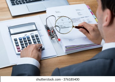 High angle view of businessman examining invoice with magnifying glass at office desk