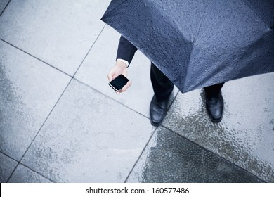 High angle view of businessman holding umbrella and looking at his phone in rain