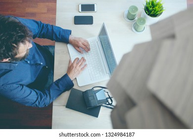 High angle  view of businessman with laptop computer on wooden table using laptop while sitting at home