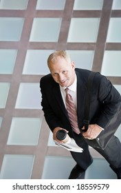 High angle view of businessman standing with briefcase and coffee in the morning