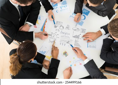 High Angle View Of Businesspeople Analyzing Graph In Office