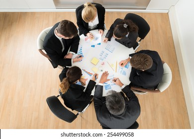 High Angle View Of Businesspeople Discussing Graph In Office