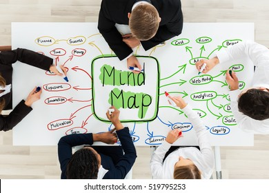 High Angle View Of Businesspeople Drawing The Flowchart Of Mind Map Concept On Office Desk In Office