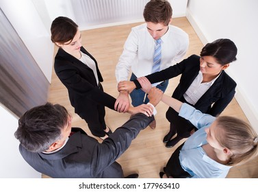High Angle View Of Businesspeople Holding Wrist