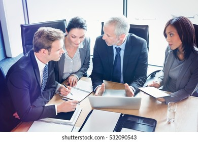 High angle view of businesspeople interacting at meeting in conference room at office