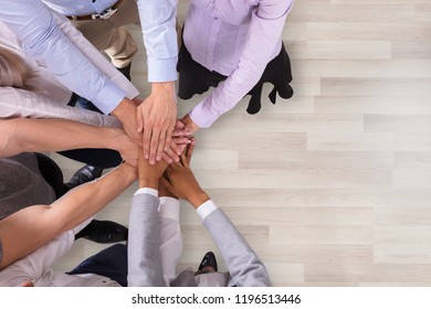 High Angle View Of Businesspeople Stacking Their Hands In Office