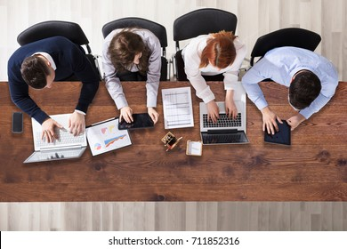 High Angle View Of Businesspeople Working In Office Over Wooden Desk