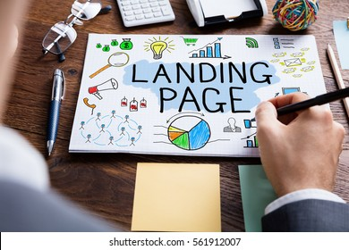 High Angle View Of Businessperson Drawing Landing Page Concept At Wooden Desk