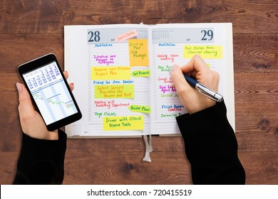High Angle View Of A Businessperson With Mobile Phone Writing Schedule In Diary