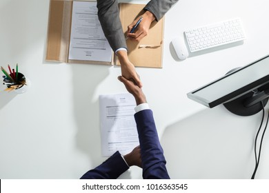 High Angle View Of Businessperson Shaking Hand With Candidate Over White Desk - Shutterstock ID 1016363545