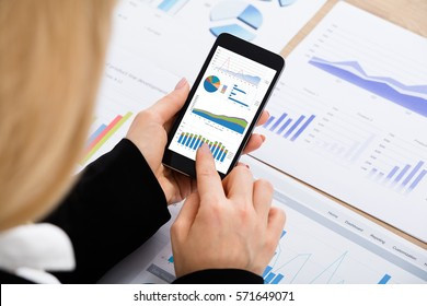 High Angle View Of A Businesswoman Analyzing Graph Using Mobilephone At Office Desk