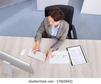 High Angle View Of Businesswoman Smiling Young Businesswoman At Desk