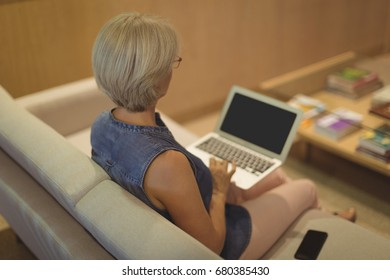 High angle view of businesswoman using laptop while sitting on sofa in office