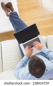 High angle view of casual man typing on laptop with feet on table in bright living room