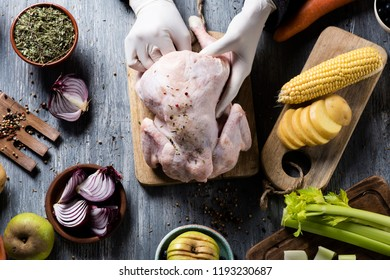 high angle view of a caucasian man, wearing gloves, preparing a turkey, placed on a rustic wooden table full of ingredients to stuff it such as apple, onion, celery and different spices