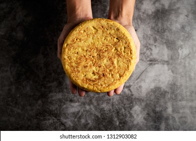 high angle view of a caucasian man with a typical tortilla de patatas, spanish omelet, on his hands, on a gray stone surface