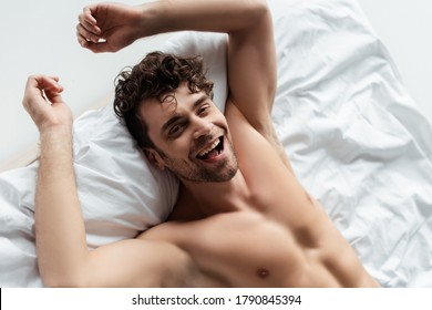 High angle view of cheerful shirtless man smiling at camera on bed isolated on white