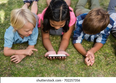 High angle view of children using mobile phone while lying on field in yard