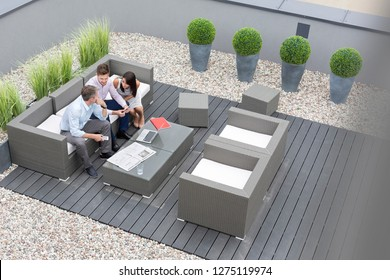 High angle view of colleagues with digital tablet sitting at office terrace