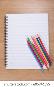 High angle view of colored pencils lying against blank spiral binder