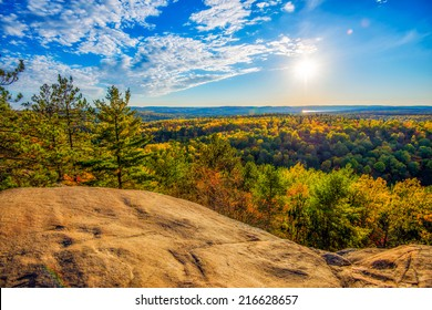 A high angle view of the colorful autumn treetops viewed from above on a rocky cliff.  Golden sunlight shines down on the landscape with soft clouds in a blue sky.
