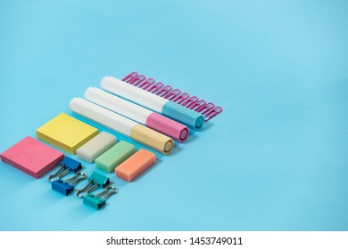 High angle view of colorful sticky notes, stationery, marker and paperclip on pastel blue background with copy space