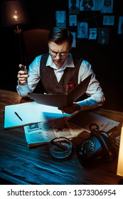High angle view of concentrated detective in glasses reading dossier in dark office
