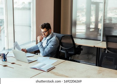 High angle view of concentrated IT worker with papers looking at laptop at table in coworking space