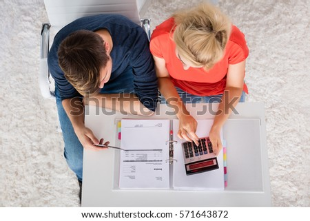 High Angle View Of Couple Calculating Invoice, Money And Family Budget On Desk At Home