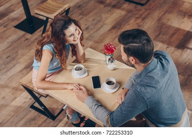 high angle view of couple holding hands while having date in coffee shop