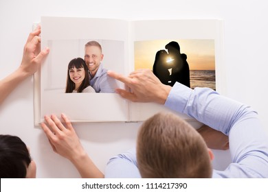 High Angle View Of A Couple Looking At Their Photo Album Over White Background