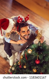 High angle view of couple in love, wearing Santa hats, decorating Christmas tree. Man piggybacking his girlfriend while she places Christmas star on the top of the Christmas tree
