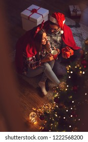 High angle view of couple in love sitting next to a nicely decorated Christmas tree, covered with soft red blanket, hugging, drinking hot tea and exchanging presents