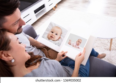 High Angle View Of An Couple Sitting On Sofa Looking At Photo Album