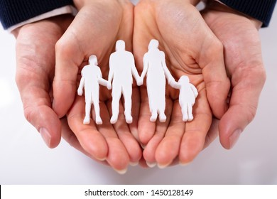 High Angle View Of Couple's Hand With Family Figure Over White Surface