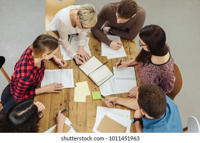 High angle view of co-workers cooperating while working with papers at table in office