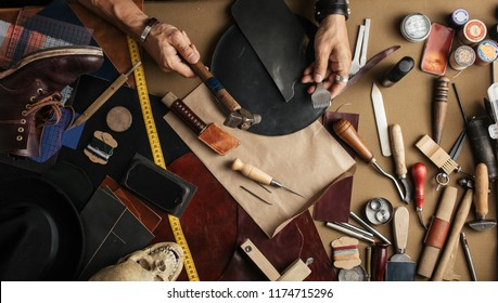 High angle view of craftsman at work over background with set of cobbler tools and colored leather in rolls. Genuine leather handbag master at work in local workshop. Handmade concept.