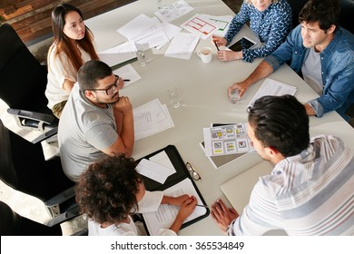 High angle view of creative team sitting around table discussing business ideas. Mixed race team of creative professionals meeting in conference room.