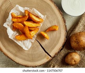 High angle view of crispy fried potato, served on wood