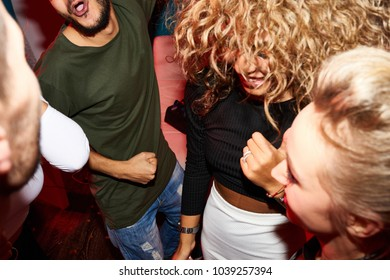 High angle view at crowd of excited dancing people in nightclub, shot with flash
