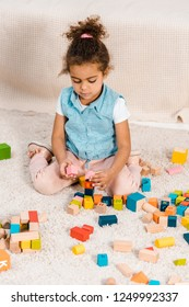 high angle view of cute african american child sitting on carpet and playing with colorful wooden blocks