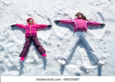 High angle view of cute daughter and mother playing and lying in the snow. Happy woman and smiling little girl having fun in snowdrift. Cheerful family making snow angel while lying on snow.