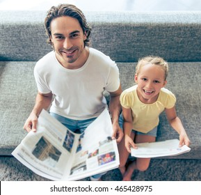 High angle view of cute little girl and her handsome father reading newspapers, looking at camera and smiling while sitting on couch at home