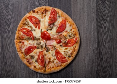 High angle view of delicious Italian pizza with ham and tomatoes on gray wooden table