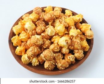High angle view of delicious popcorn in round wooden plate isolated on white background. Include buttery caramel corn and rich cheddar cheese corn. Food and snack concept.