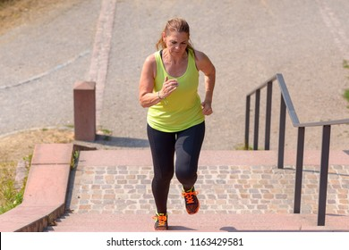 High angle view of a determined middle-aged woman running while climbing stairs during cardio workout outdoors in a sunny day of summer