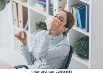 high angle view of diseased adult businesswoman spraying her nose at office
