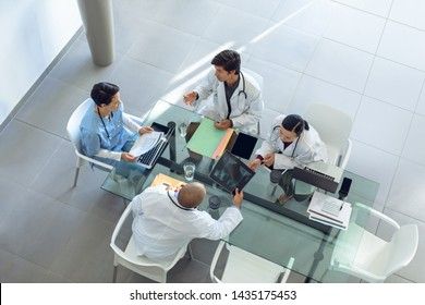 High angle view of diverse medical team discussing with each other at the table of conference room in hospital