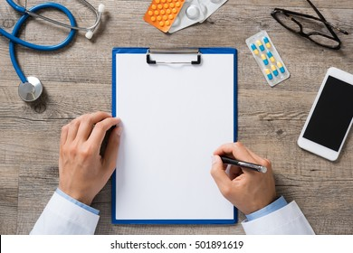 High angle view of doctor hand writing prescription on paper. Top view of hand of doctor writing on white blank paper with medicine and capsule on a wooden table. Health and medical concept.